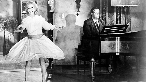 Victor Buono plays the unctuous ne'er-do-well musician named Edwin Flagg who is helping Baby Jane relaunch her career.